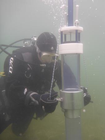 Bohrung unter Wasser: Der Taucher schlägt mit einem Schwinghammer die Röhre in den Seeboden.