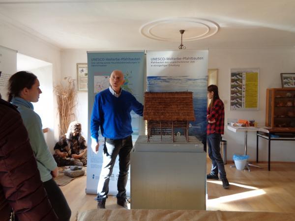 """Arnold Mörzinger vom Verein """"Freunde der Archäologie"""" erklärt ein prähistorisches Hausmodell."""