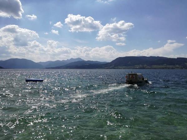 Unser Forschungsboot vor der malerischen Kulisse am Attersee (Bild: Ostrowski - Kuratorium Pfahlbauten)